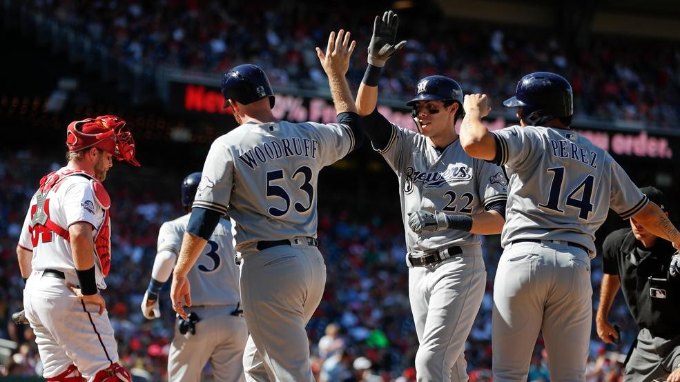 b507cebeb Milwaukee Brewers' Christian Yelich (22) is greeted at home by teammates  Brandon Woodruff (53) and Hernan Perez (14) after hitting a grand slam off  ...